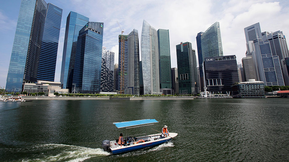 A boat manoeuvres in front of skyscrapers of the Marina Bay Financial Centre in Singapore July 12, 2012.